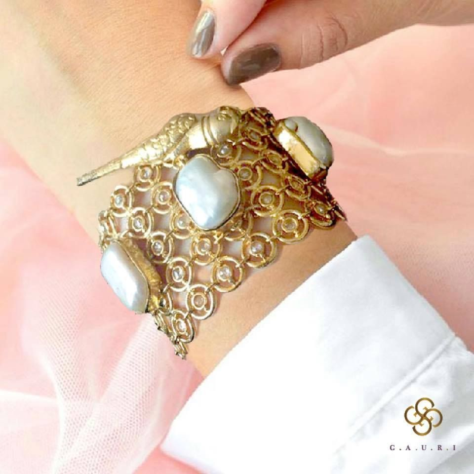 This gold bracelet is made of metal and embellished with pearl work