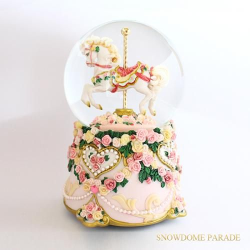 A snow globe of a pink roses merry-go-round.