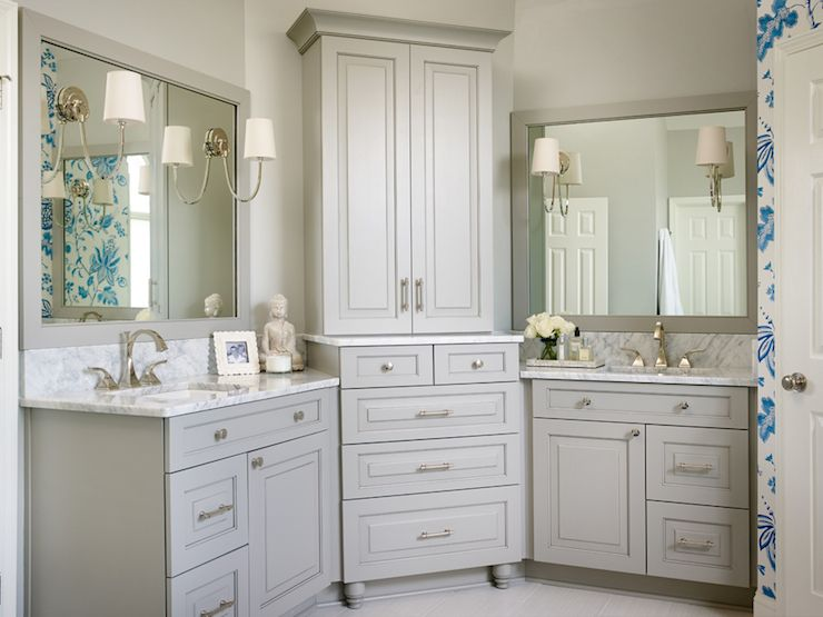 beautiful bathroom features gray his and hers vanities topped with white marble under gray mirrors illuminated