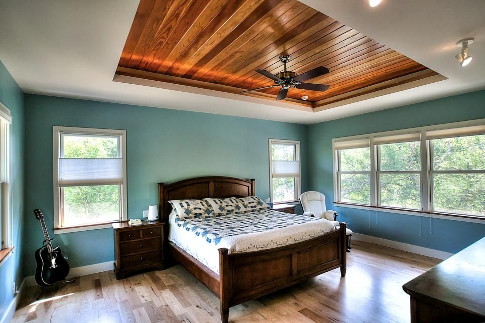 A wood paneled tray ceiling adds warmth to this turquoise