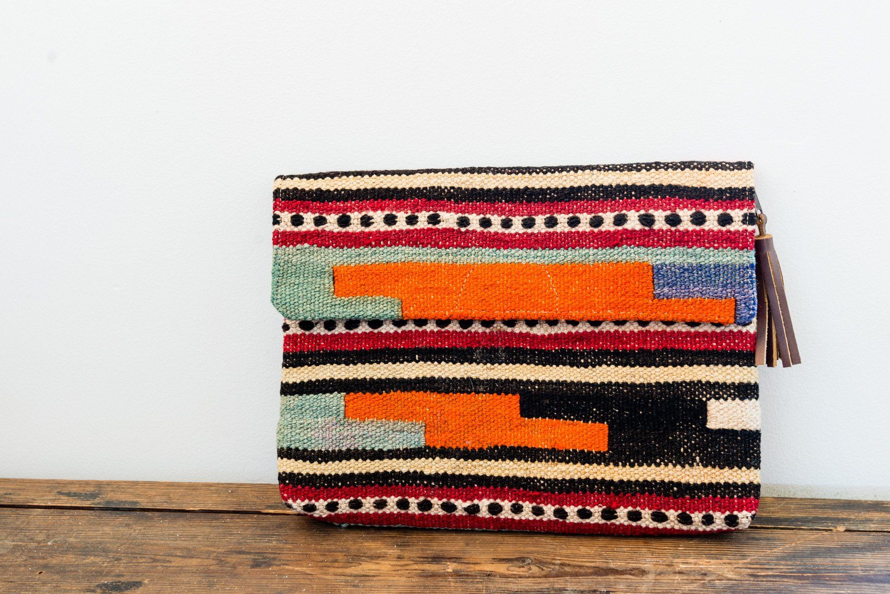 """This double-sided clutch has a fold over flap. This clutch is the perfect blend of classic and modern. It can be used as a clutch or a purse. Brought to us by Togar Rugs itwas handmade in Istanbul, Turkey from a Kilim rug. Each purse is one of a kind! For more on Togar Rugs and how it was madeclick here. Dimensions: 11"""" long x 7.5"""" tall x 3"""" wide Wool from Kilim Rug on both sides Handmade"""