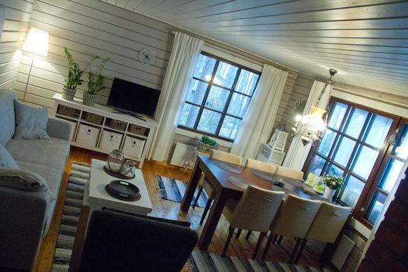 mökki,olohuone,ruokailuryhmä,ruokailutilat,suuret ikkunat,valoisa,moderni,vaalea,verhot,ruokatuolit,sohvaryhmä,sohvapöytä