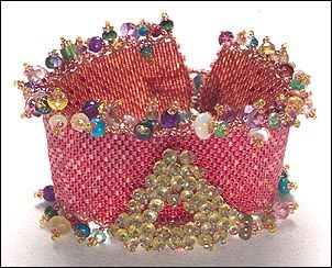 Articulated components are dazzling in beadwork. This very contemporary design incorporates an embellished revolving triangle that is attached in the center of a flat peyote stitched band. The band is a blending of color and finish for a painted look. The edges of the bracelet are embellished with a fringe technique. Close the bracelet with a beautiful button and loop.