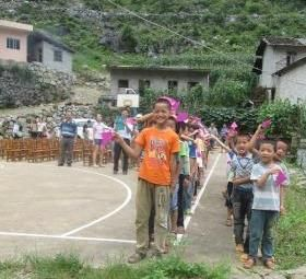 The kids were all lined up on the playground to sing for us when were arrived.