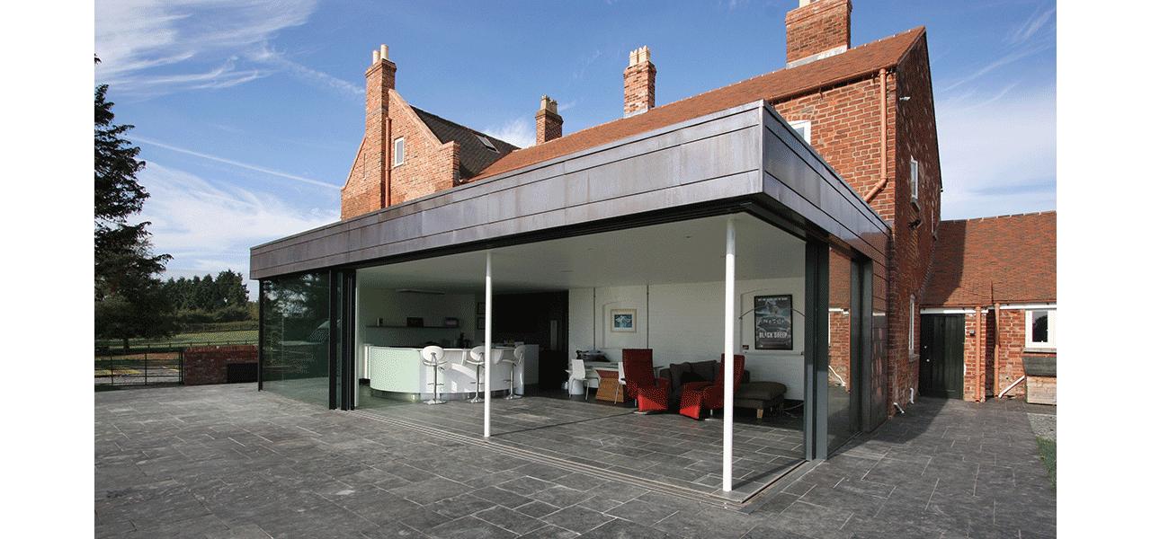 Modern extension to Grade II listed farm house using IQ's minimal windows 4+ sliding glass doors