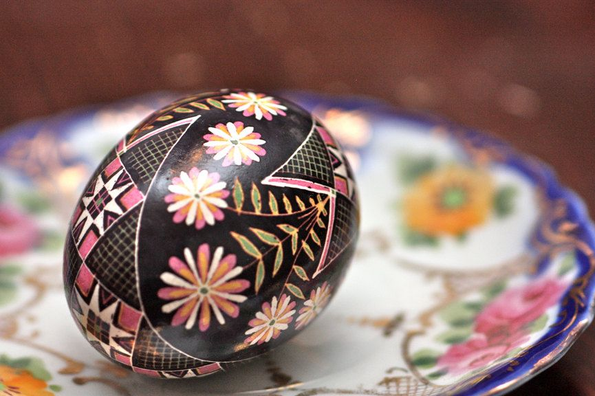 Ring-Around-The-Rosy Pysanky Egg: A Garland of Pink, Yellow and White Blooms Encircles Traditional Scarves on Black Background. $93.00, via Etsy.