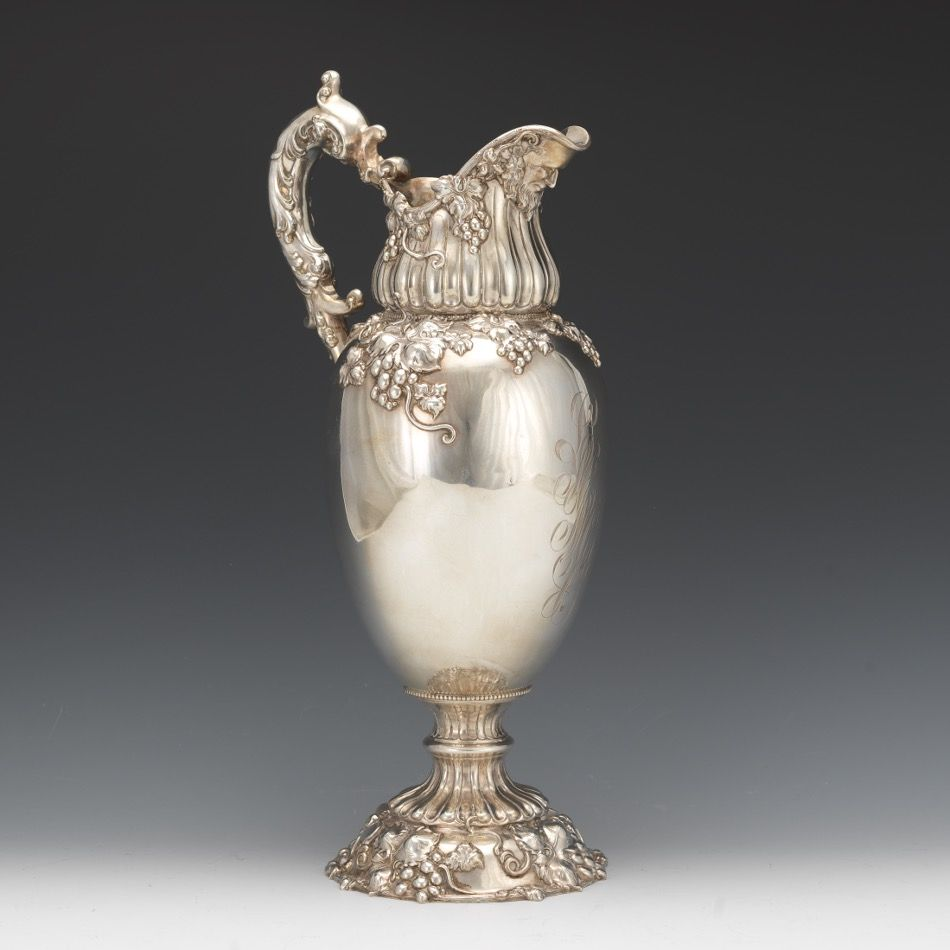 "Attributed  Arthur Stone for Frank W. Smith  - Sterling Silver Large Ewer, Retailed by W.W. Wattles & Sons, ca. Early 20th century - Cast sterling silver ewer with pronounced spout with grotesque mask, applied ""S"" scroll handle with thumb piece; on fluted baluster stem and circular dome foot with serpentine rim. Richly decorated with high-relief cast and hand chased grape clusters and vines, monogrammed. Marked with Frank W. Smith hallmark, ""Sterling"", W.W. Wattles & Sons and ""1268"" -  H:15…"