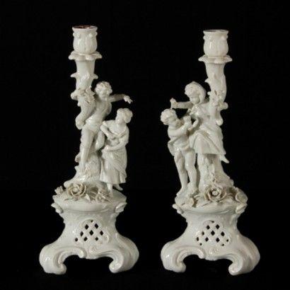 coppia-candelabri. Fine '800 primi '900  Origine: Capodimonte  Descrizione: In porcellana bianca raffigurante scena amorosa di giovane coppia. Piccole imperfezioni e marchio della manifattura sotto la base.