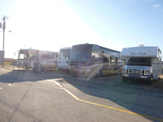 A row of stored RVs. Happy campers, that just aren't camping right now
