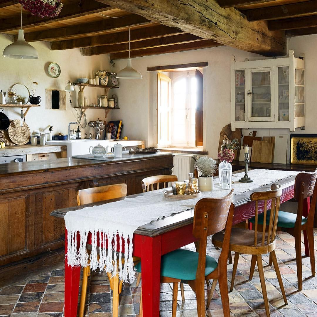 A red farmhouse table and mismatched chairs provide a