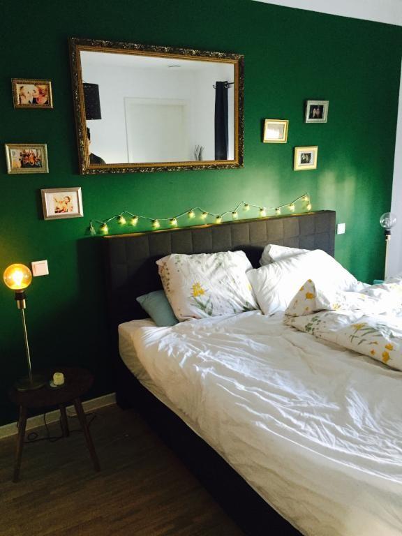Schlafzimmer mit dunkelgrner Wand und Goldrahmenfotos dunkelgruen darkgreen Wandfarbe