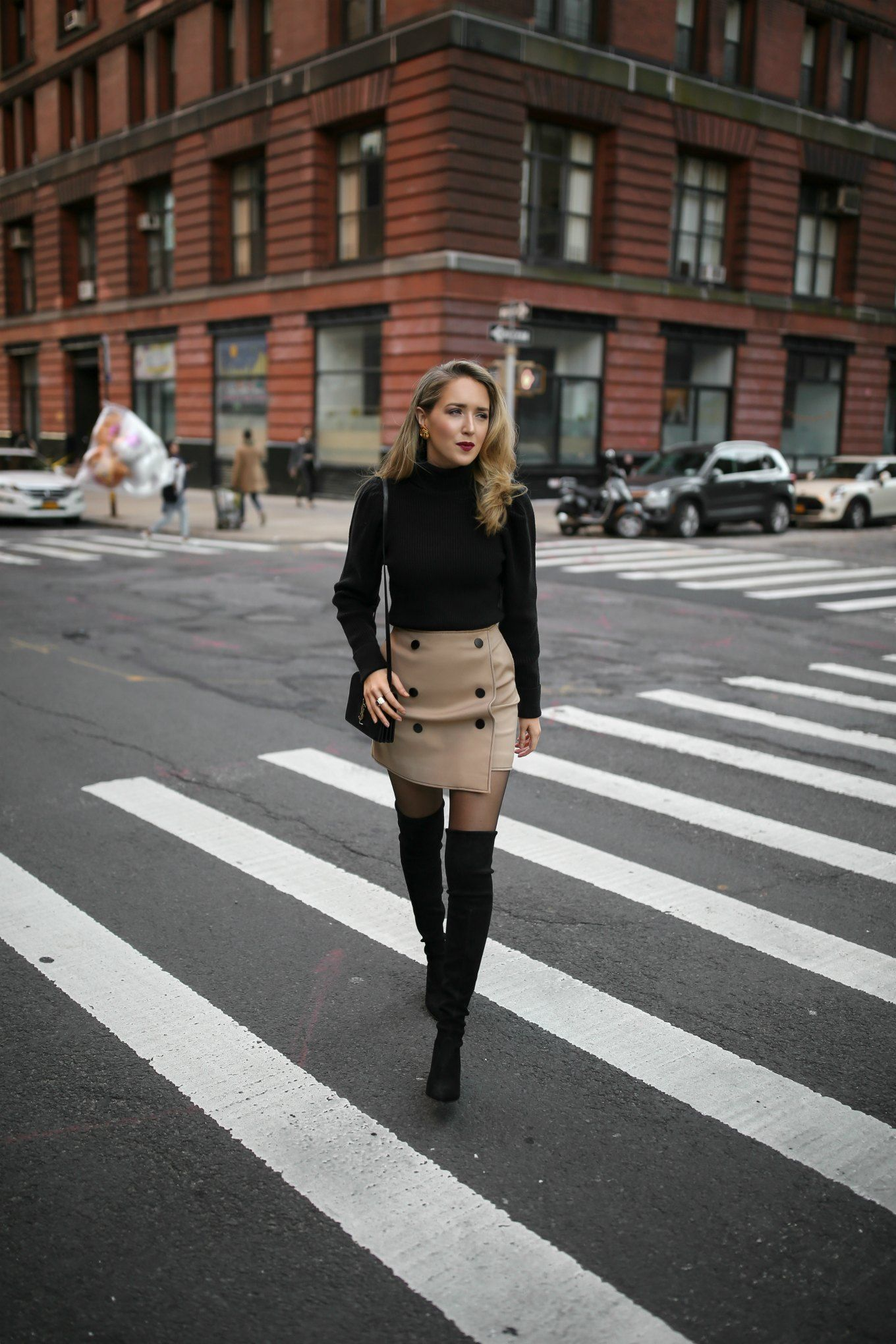 55a0bb214e50 NYC fashion blogger Mary Orton of Memorandum wears a black puffed-shoulder  turtleneck, a khaki mini skirt and black Stuart Weitzman over-the-knee boots