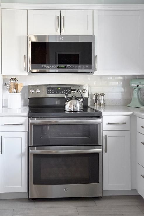 White Shaker Lowe S Arcadia Cabinets Frame A Ge Stainless Steel Microwave Mounted Above Oven Range Positioned On Style Selections Leonia Silver