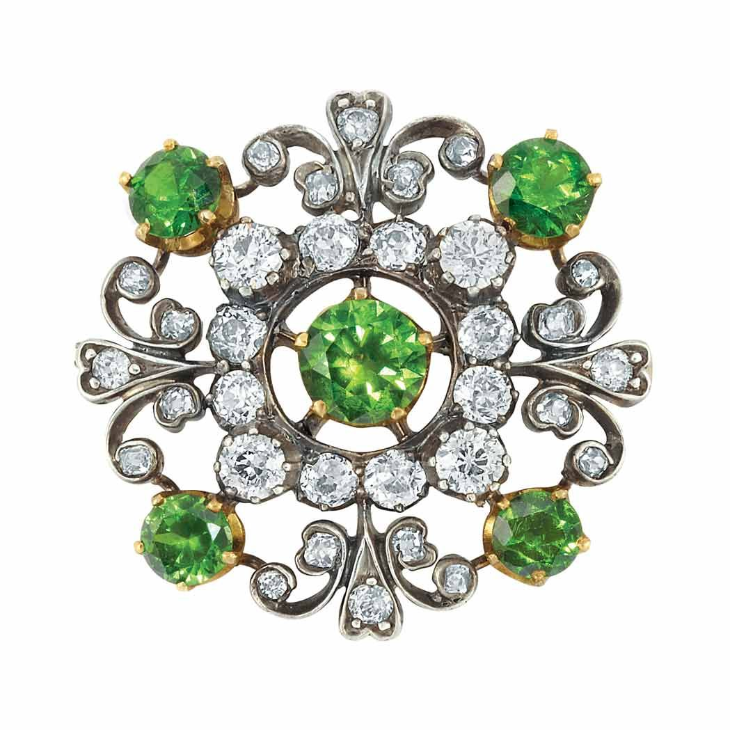 Antique Silver, Gold, Demantoid Garnet and Diamond Brooch The openwork brooch centering and quartered by 5 round demantoid garnets approximately 3.50 cts., encircled by 12 old European-cut diamonds approximately 1.70 cts., quartered by diamond-set scroll work, approximately 6.2 dwt.