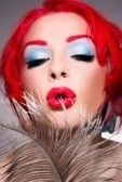 Lipstick redhead woman blowing on feather