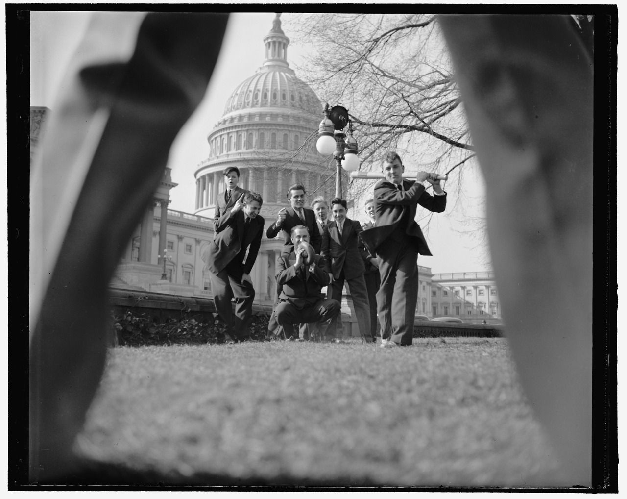 """ca. 1939. """"Baseball game with group of men and young boys (pages?) seen through legs of pitcher, with U.S. Capitol in background, Washington, D.C.""""Harris & Ewing Collection, Library of Congress."""