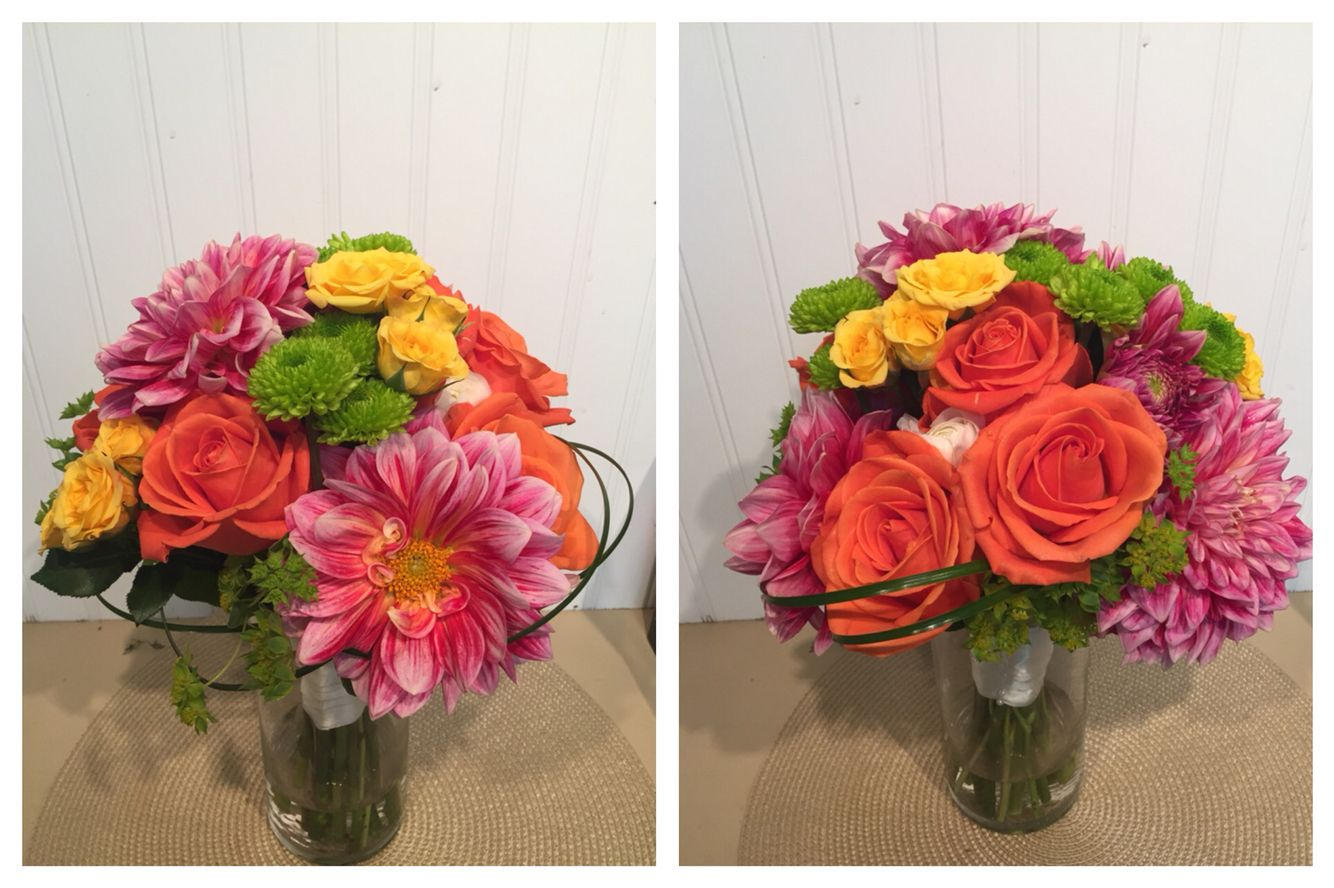 A bright bridal bouquet with orange roses, pink dahlias, yellow spray roses, and green buttons. From T&V Floral
