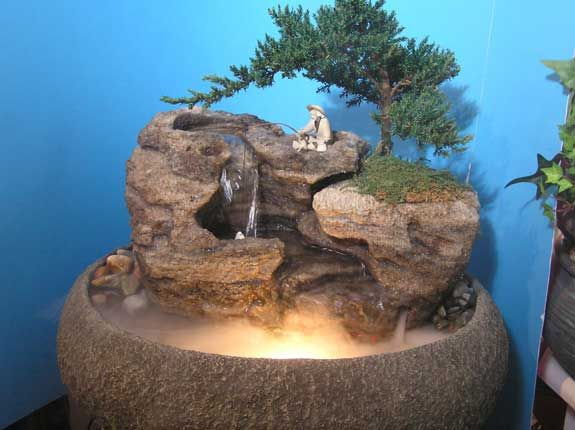 this live bonsai tabletop fountain features natural cascading waterfalls and fisherman actually fishing in the waterfall - Tabletop Fountains