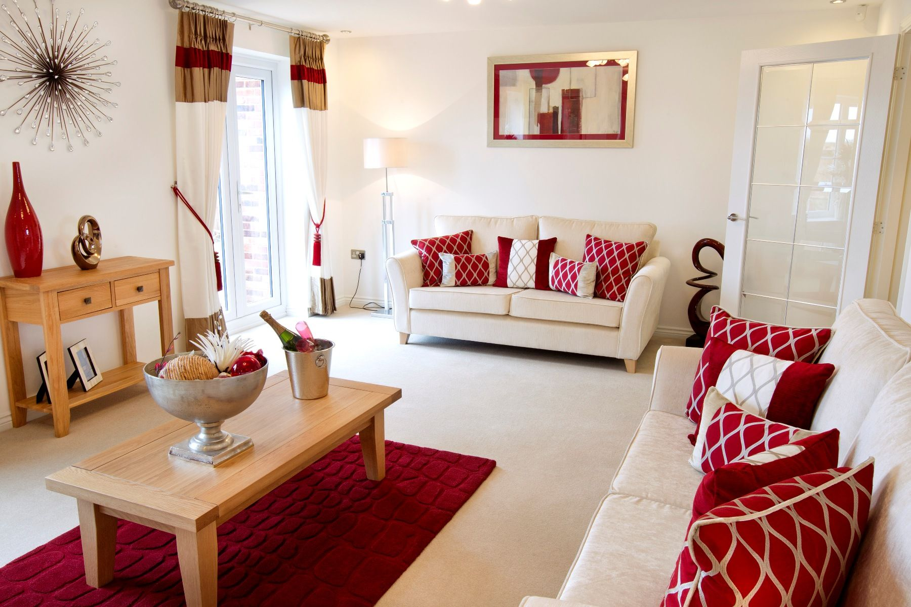 Red hues complement the welcoming cream interior of this for Cream living room designs