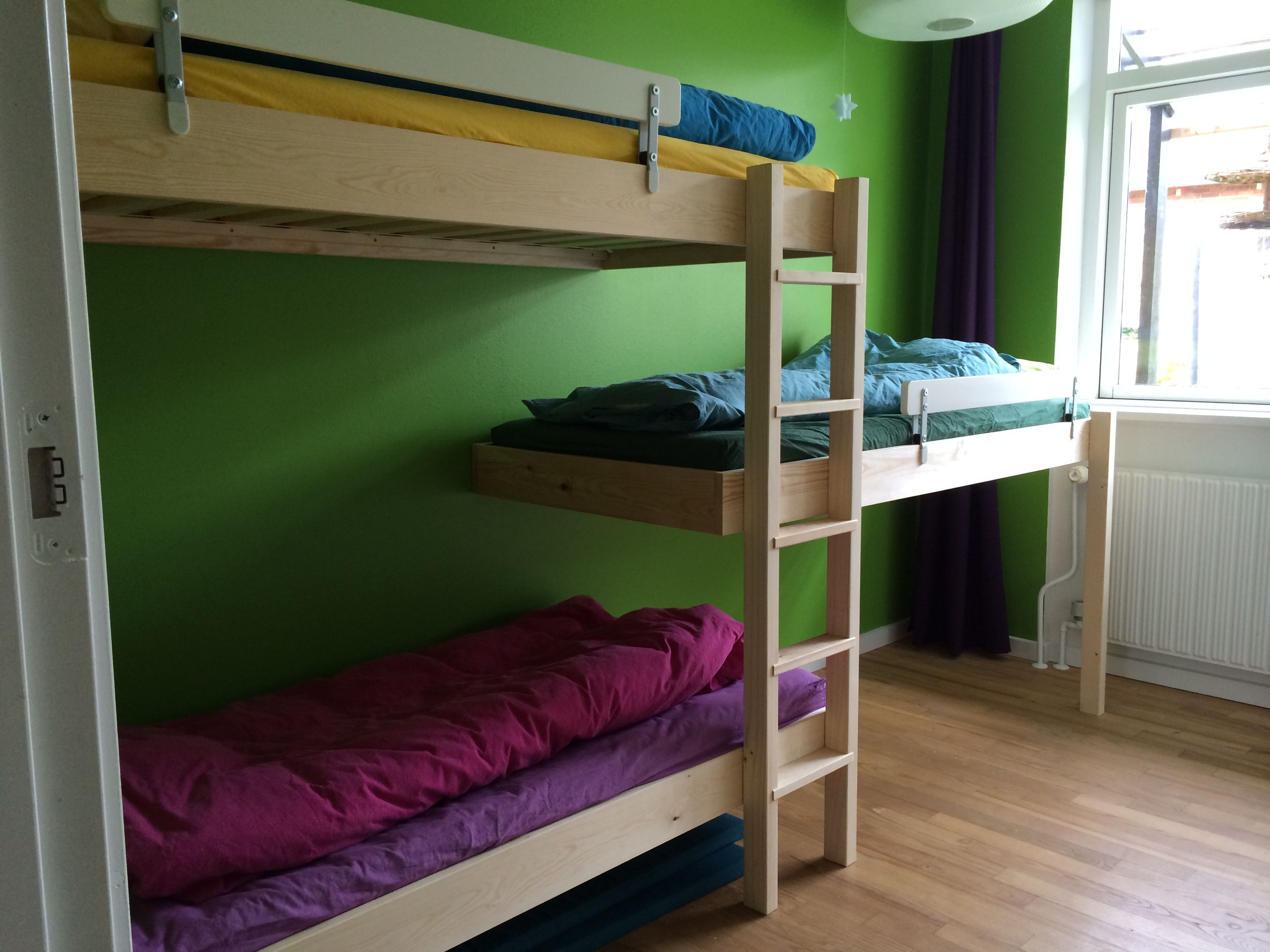 Triple bunk bed in room with low ceiling. Three frames and