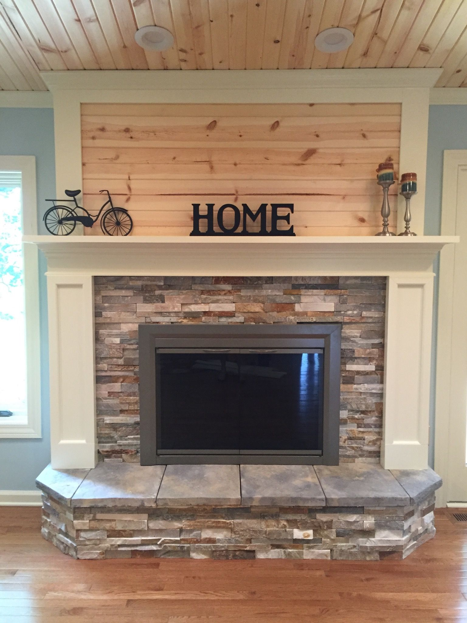 Fireplace update with stacked stone painted wood and knotty pine