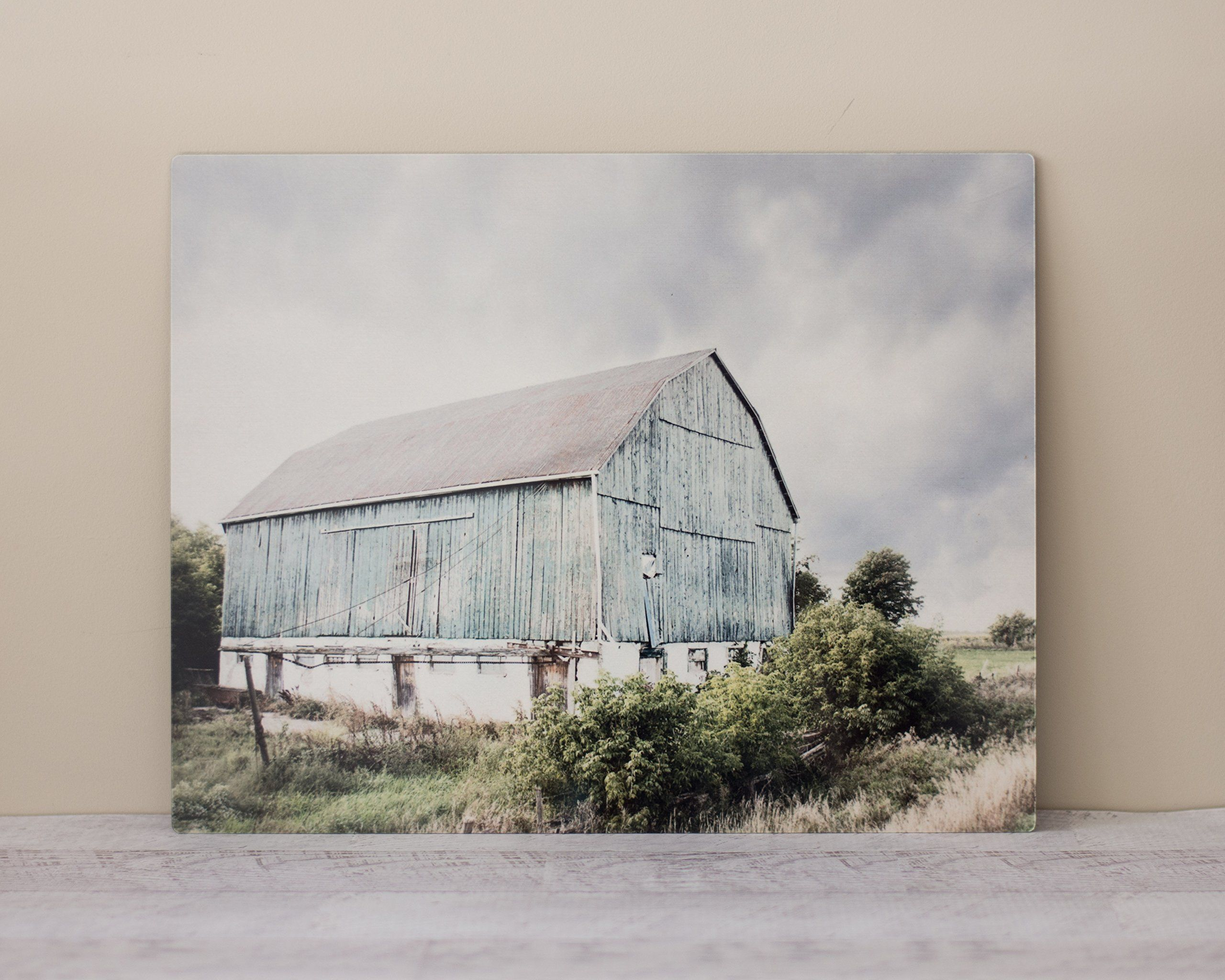 Modern Country Artwork, 11x14 Horizontal Metal Print. This 11x14 ready to hang aluminum metal print features an photograph of a rustic turqoise barn. The image is printed on 0.1 inch thick aluminum. The print is coated with a protective reflective finish bringing an ultra-modern feel to your walls. A 1/2 inch float mount notched block hanger is installed for easy hanging. The piece is finished of with rounded corners.