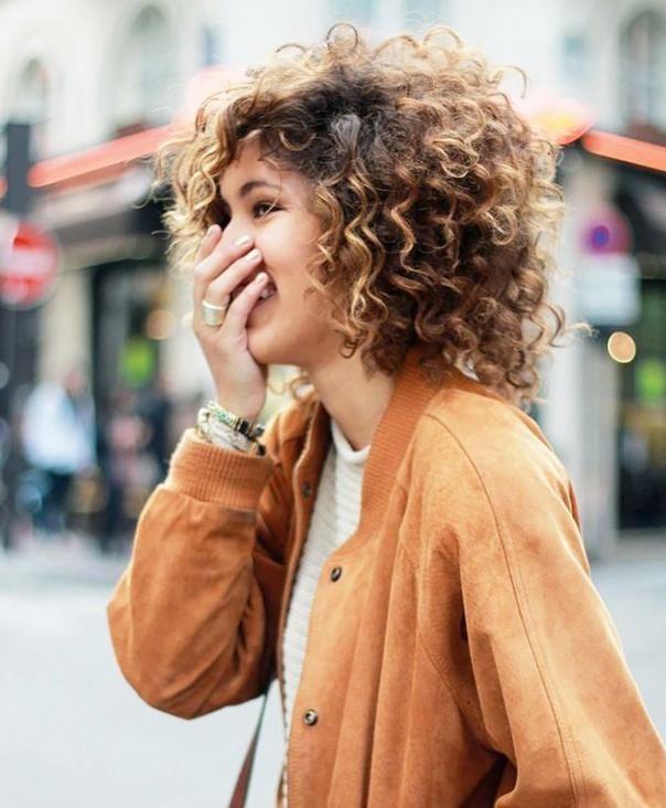 Jeune femme dans la ville, cheveux bruns courts bouclés