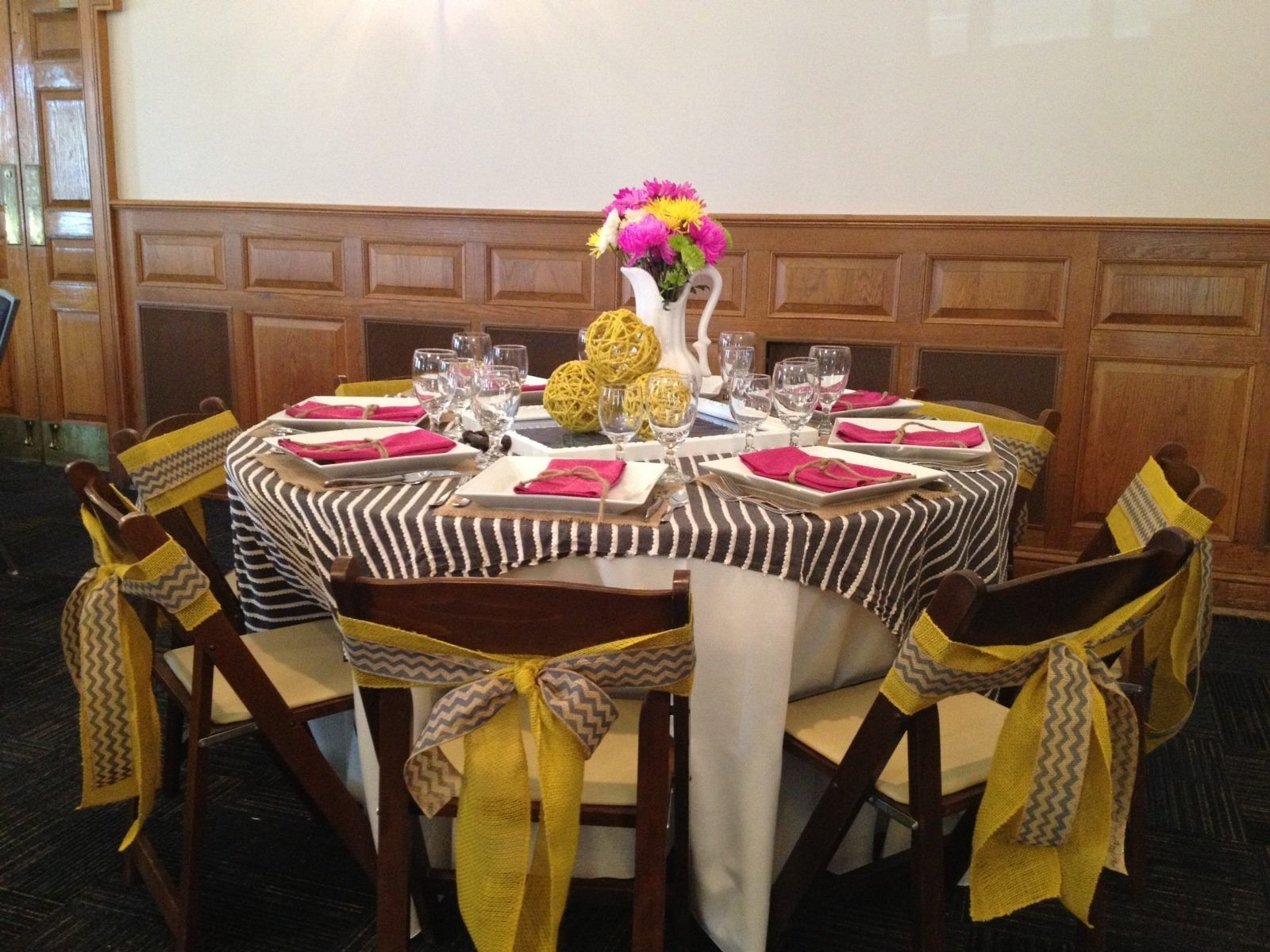 Easy summertime table setting. Striped fabric overlapped makes an inexpensive but interesting table topper. Burlap ribbon for chair backs.