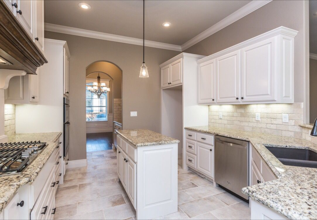 Spacious kitchen with custom white cabinets, light travertine ...