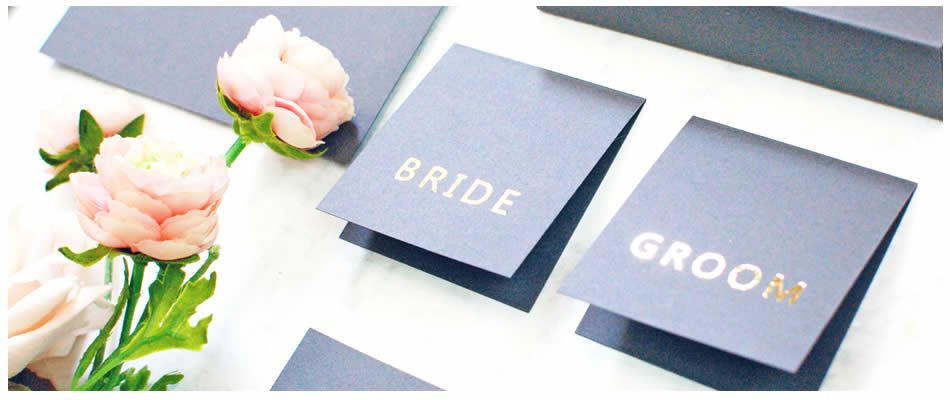 Grey and gold place cards printed with guest names in gold foil to place on tables at the wedding meal