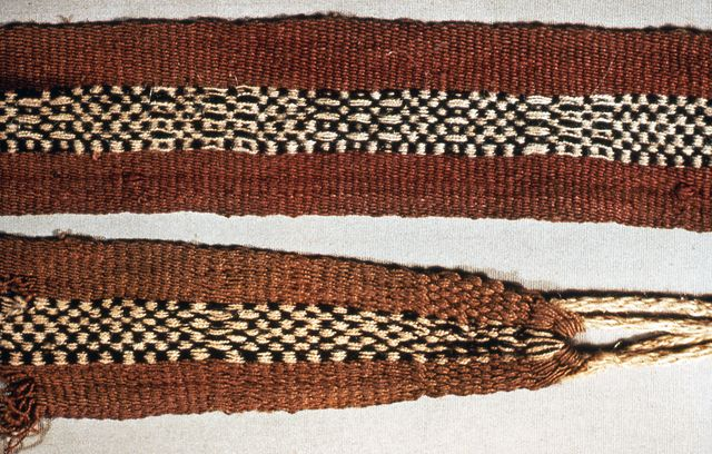 """Belt of dark red wool with center design of black and white checker pattern. White cords to tie at sides.    This belt is medium: wool technique: warp-faced plain weave with float patterning; warp selvages; sides intact.    This belt is from Peru and dated """"possibly 1200""""."""