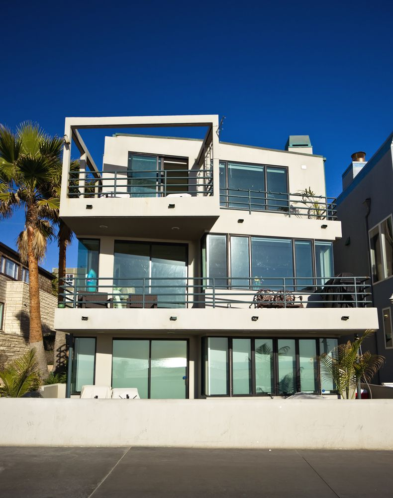 3 story heavily windowed contemporary home with multiple decks