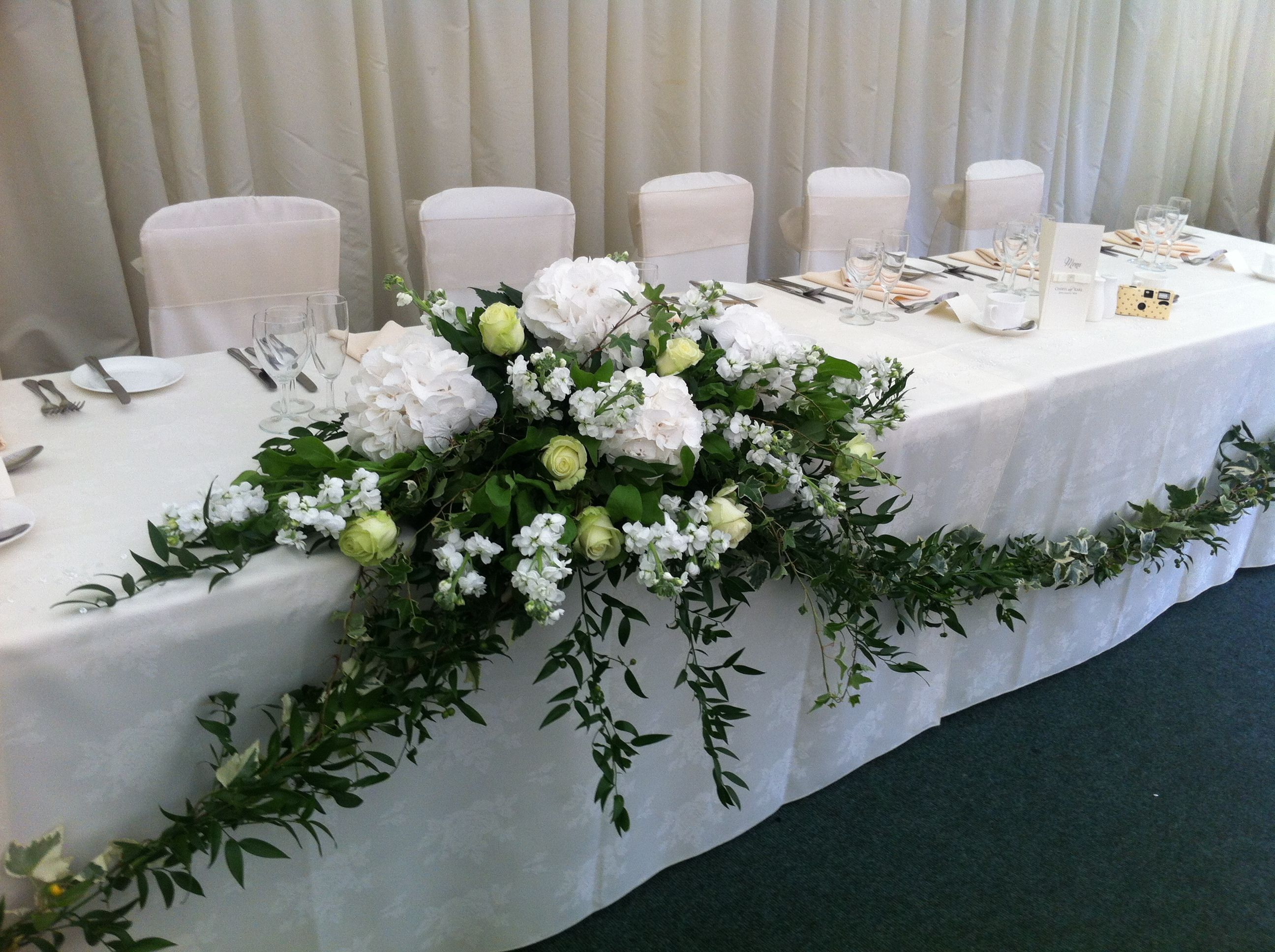 Top Table Arrangement And Foliage Garland, But Perhaps With Some Ivy Or  Something To Stop