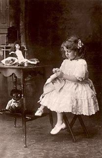 Young girl sewing- love the dolls!
