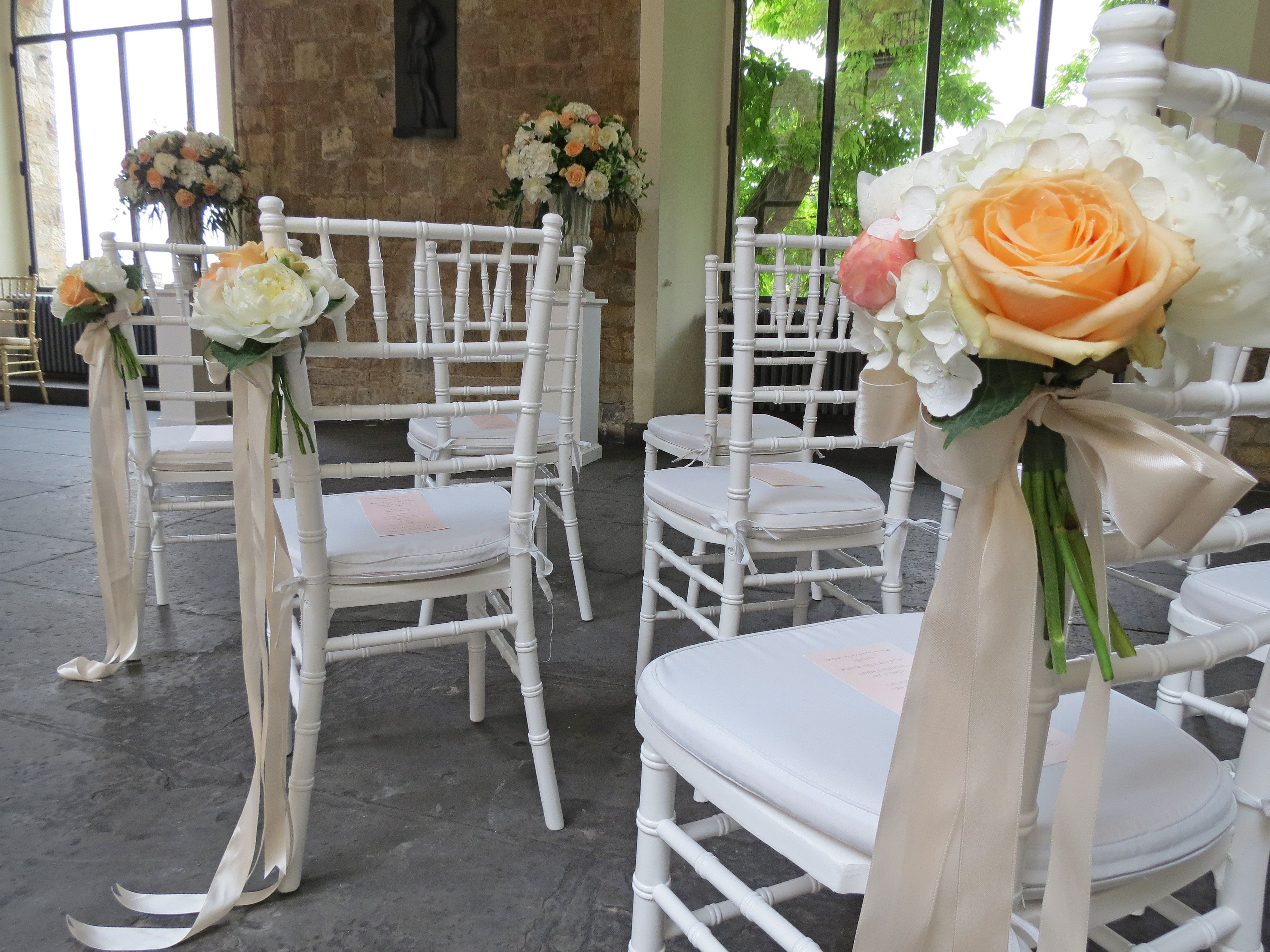 Bouquet for the chairs with white peonies and hydrangea, peach roses and ranunculus . Event Planner : Wedding Italy.