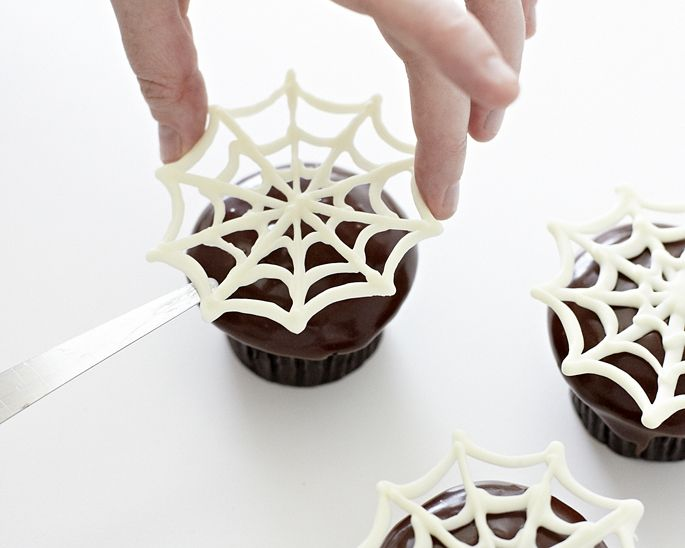 How to make spider web cupcakes - a quick and easy Halloween dessert! Learn more here: http://cakejournal.com/tutorials/easy-spider-web-cupcakes/ #Halloweendessert #Halloweencupcakes #Halloween #spiderwebcupcakes