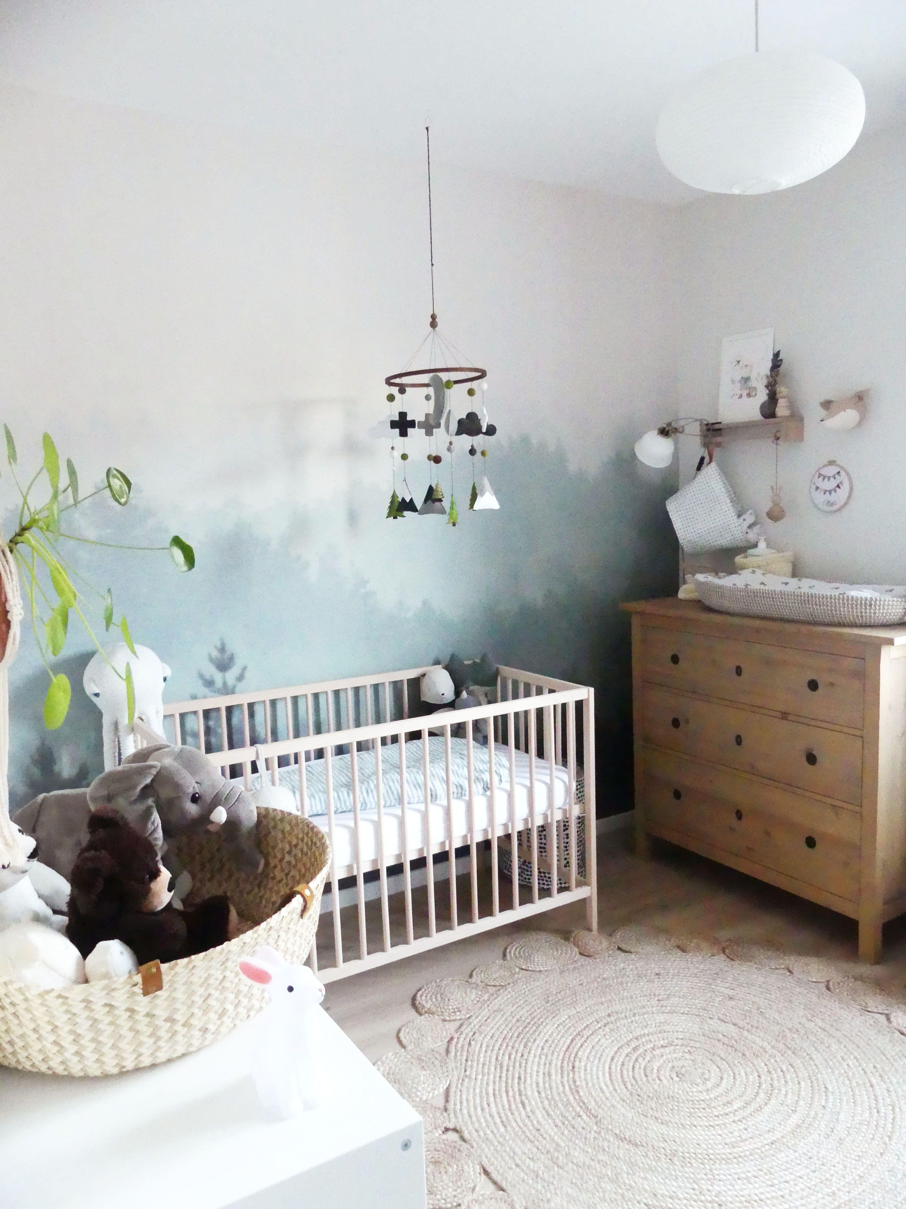 chambre de bébé mixte thème nature avec un papier peint forêt