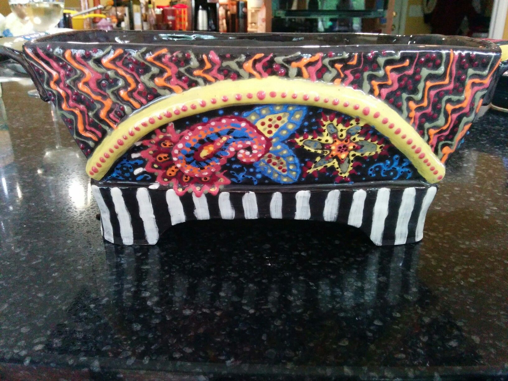 Hand built from thrown walls and decorated with colored slip.  I like Paisley