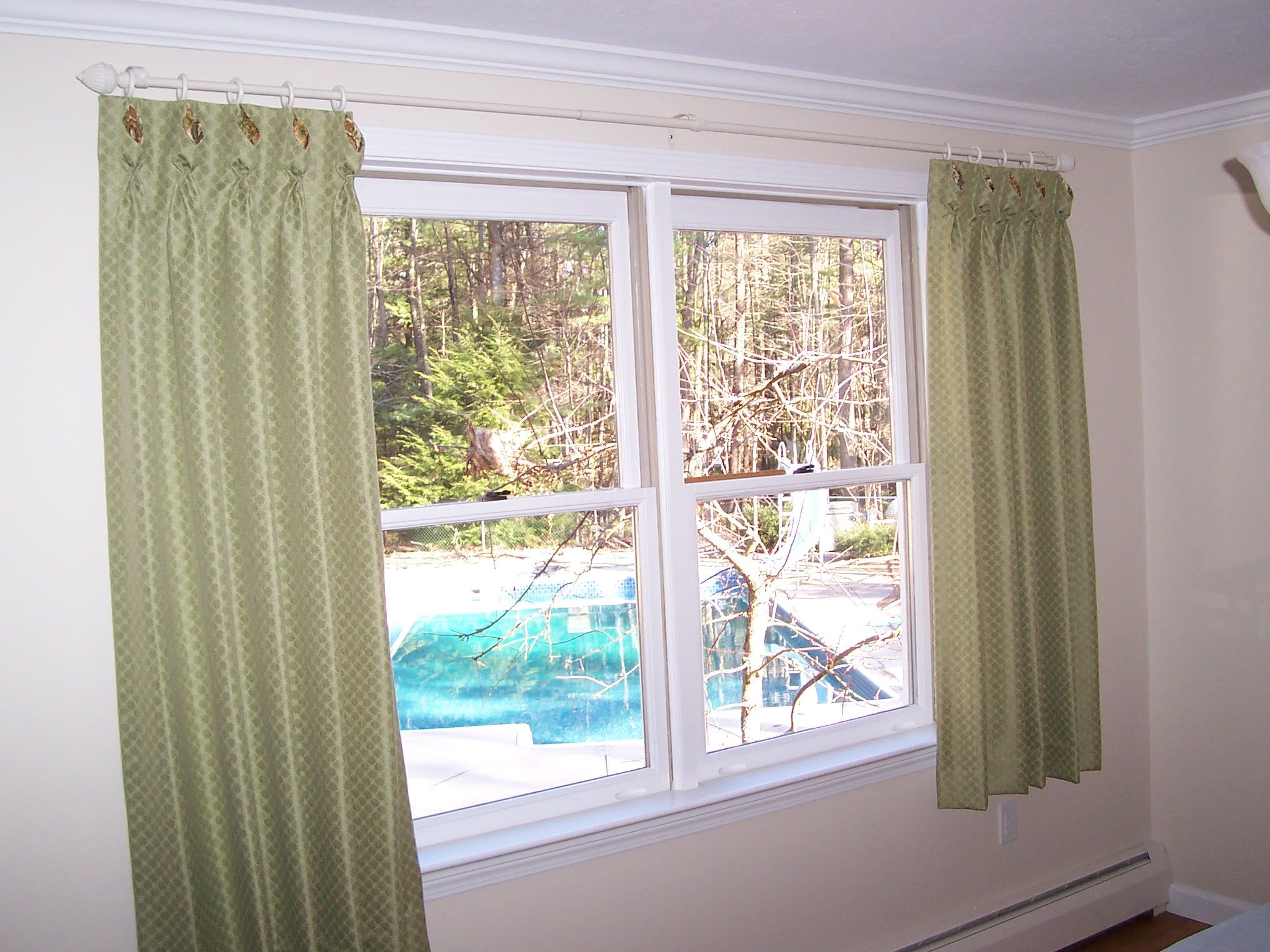 Pleated Drapes with an opened shaped pleat to show contrasting fabric on coordination valances in the  adjoining kitchen