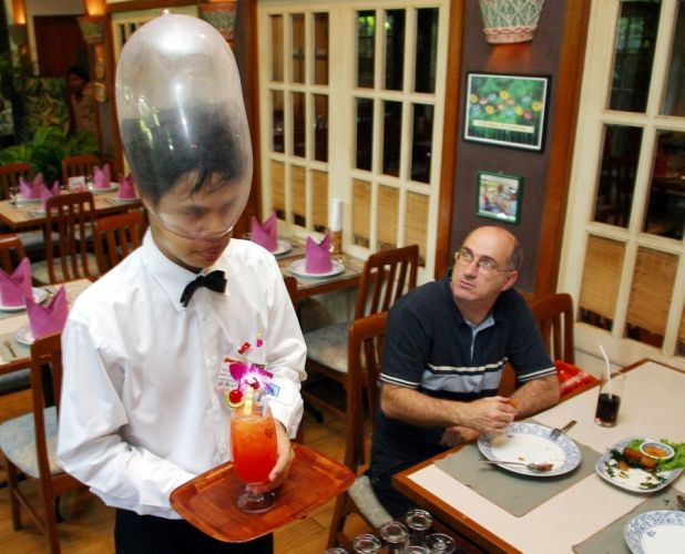 Cabbages and Condoms restaurant  A waiter serves a cocktail while wearing a condom on his head at Cabbages and Condoms, a restaurant in Bangkok that aims to educate the public about safe sex.