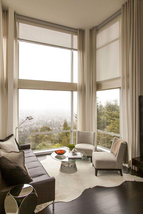 Gran combinación de cortinas y enrollables para ésta sala de estar con preciosas vistas.  Modern blinds idea for sunny condo windows. I like how light and airy it looks.