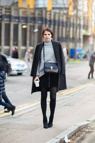 3bd19d4da2ca Winter Outfits - how to style tights: over-the-shoulder black winter coat  worn with a gray turtleneck sweater, zip mini skirt + sheer tights
