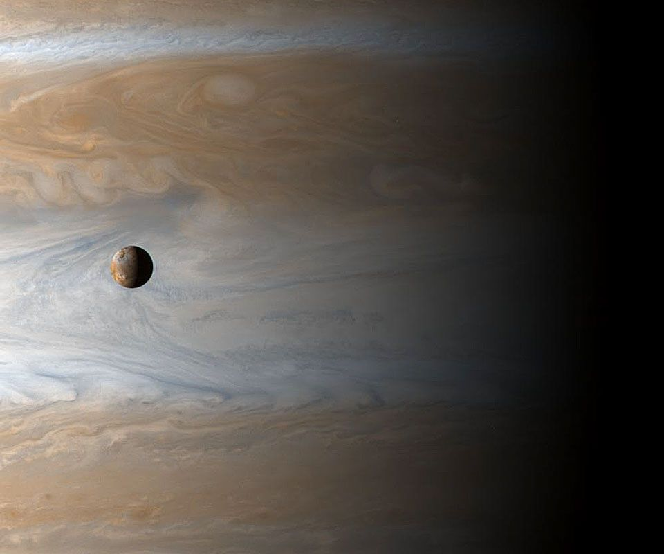 Io is one of Jupiter's moons about the size of our moon.  It travels around the giant seen behind it about once every 42 hours.  It orbits about 350,000 kilometers above those hurricanes seen on Jupiter's surface.
