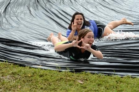 Elizabeth Oakes (front), junior public relations major, throws Kappa Delta letters and Becca Orosz, sophomore social work major, throws their family giraffe symbol on the slip 'n slide while celebrating Panhellenic Bid Day. - Photo by Anne Richoux