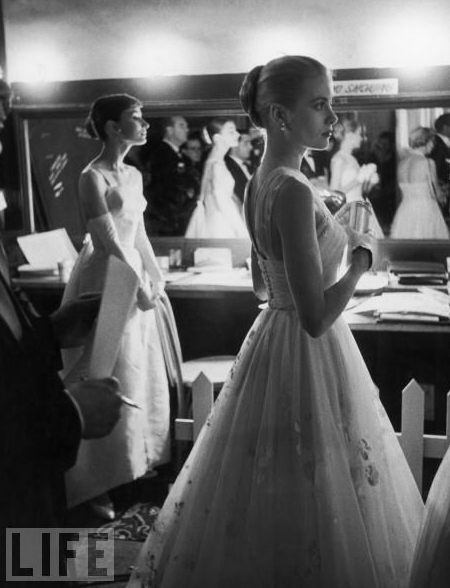 The two most elegant stars of their era, Audrey Hepburn and Grace Kelly, are photographed backstage at the RKO Pantages Theatre in 1956 as they wait to present: Hepburn gave Best Picture to Marty, and Kelly awarded the Best Actor statue to Ernest Borgnine for the same film.