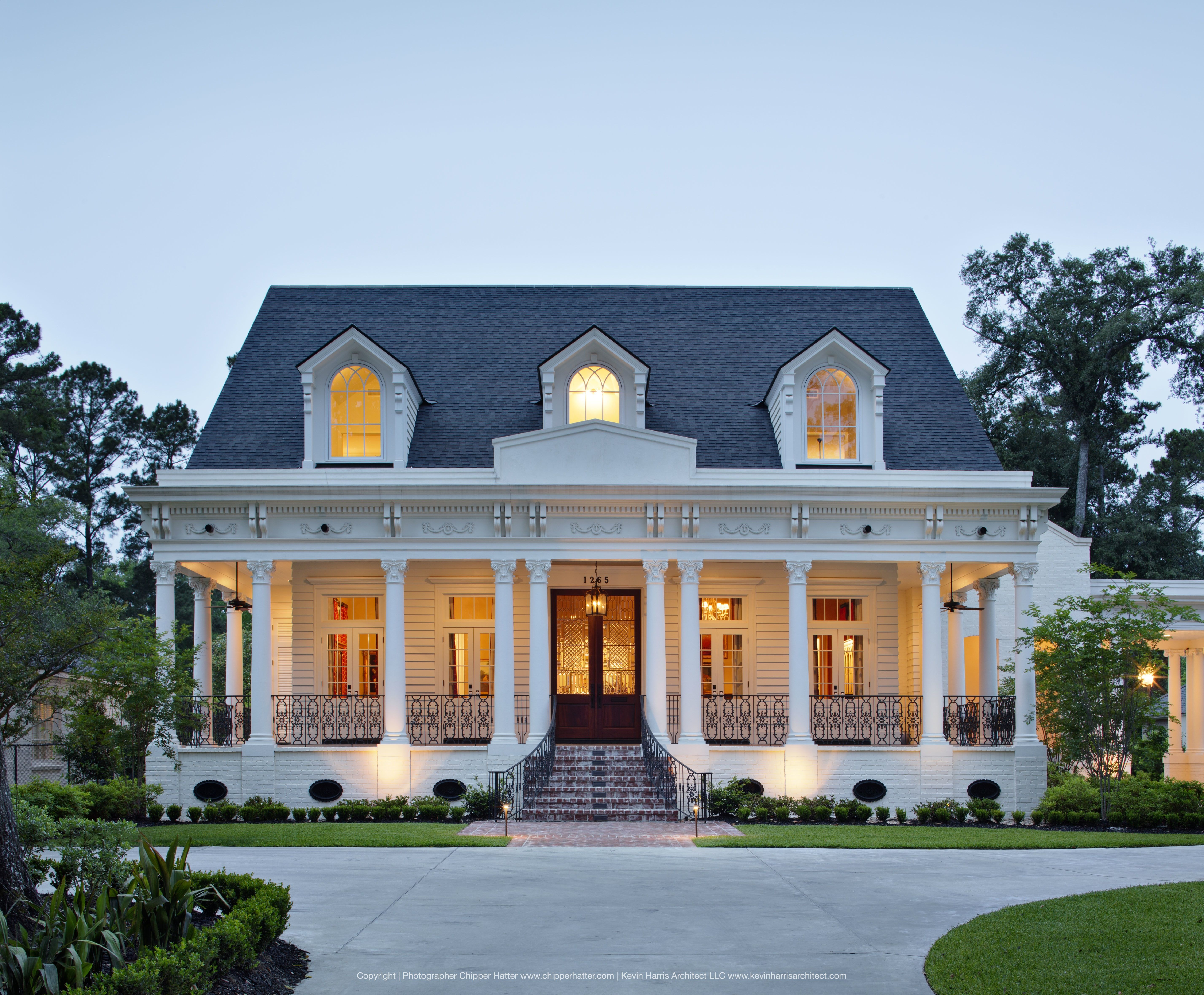 Front door at dusk with cozy porch and white columns on for Modern southern homes
