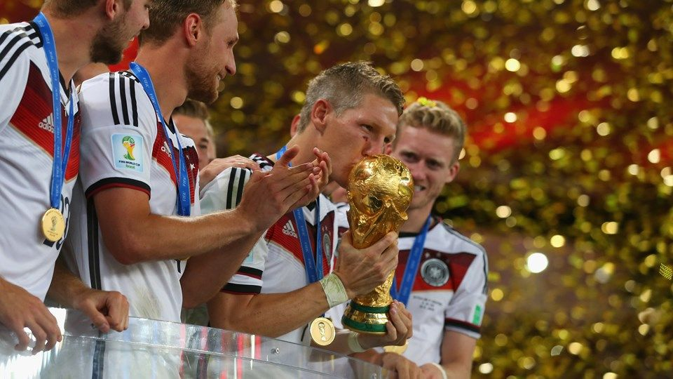 RIO DE JANEIRO, BRAZIL - JULY 13: Bastian Schweinsteiger of Germany kisses the World Cup trophy to celebrate with his teammates during the award ceremony after the 2014 FIFA World Cup Brazil Final match between Germany and Argentina at Maracana on July 13, 2014 in Rio de Janeiro, Brazil. (Photo by Alexander Hassenstein - FIFA/FIFA via Getty Images)