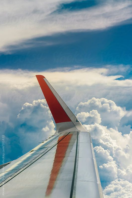 Airplane wing during a flight over a sky with clouds by Alexander Grabchilev #stocksy #realstock