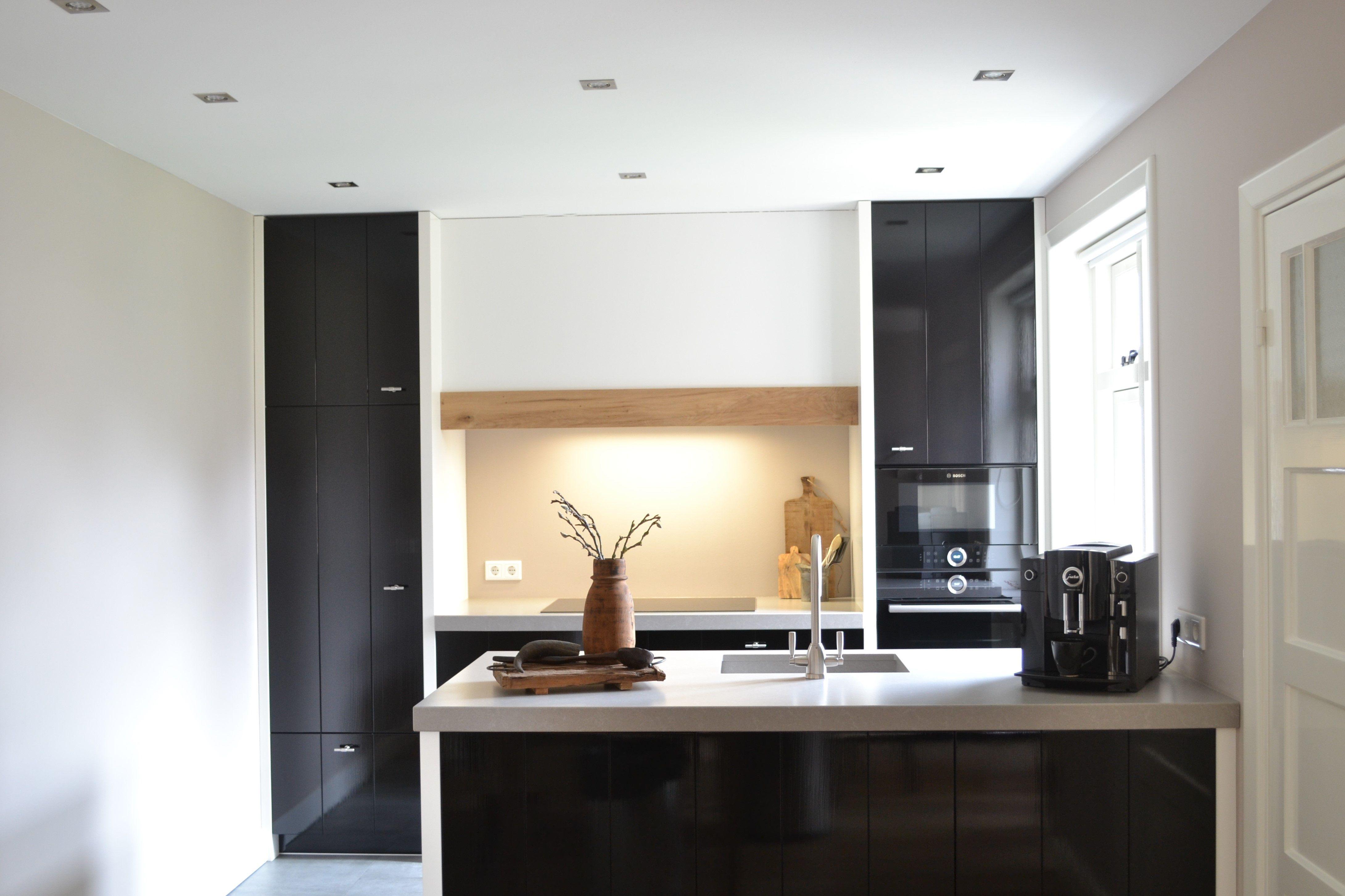 Handgeschilderde zwarte keuken met witte stolwanden en een