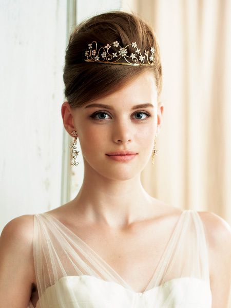 愛らしいゴールドのティアラはティアラデザイナー、紙谷太朗氏によるデザイン。逆毛を立ててトップにボリュームをもたせた夜会巻きヘアに合わせ、上品...